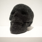 Skull (black), 2013, air rifle BBs, cast resin, mixed media, 6 x 6 x 8 in.