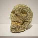 Skull (gold), 2013, air rifle BBs, cast resin, mixed media, 6 x 6 x 8 in.