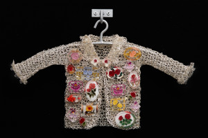 Mother Love 2, 2017, crocheted metal coat, vintage rose pins, acrylic beads, steel hanger and bracket, 16 x 10.5 x 2